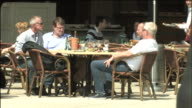 Friends relax at a sidewalk cafe.