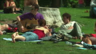 WS Friends relaxing on lawn in Retiro Park, Madrid, Spain