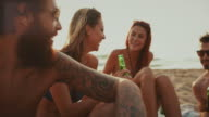Friends relaxing together on the beach at sunset