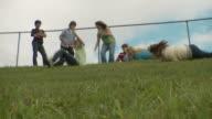 WS LA Friends (13-16) rolling down grassy hill, Cazenovia, New York, USA