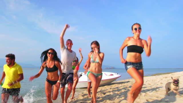 Friends running on the beach 4K