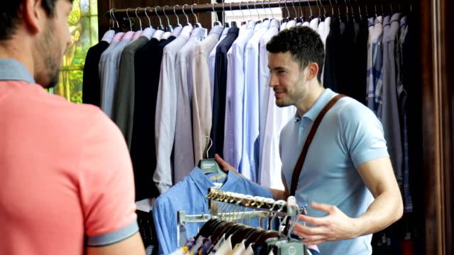 Vänner letar kläder på köpcentret