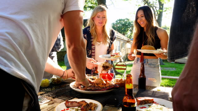 MS Friends serving barbecue in backyard on summer evening