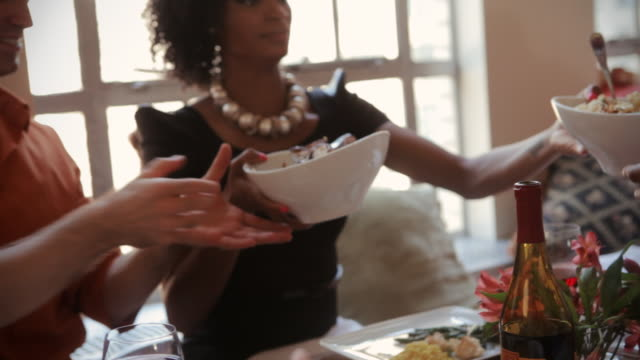 friends serving, eating and passing food at a dinner party