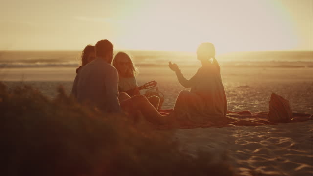 Friends sitting at beach and relacing