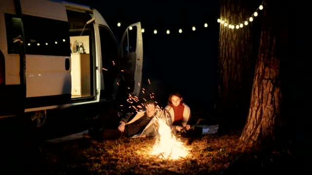 Friends sitting near campfire in the forest near the camper van