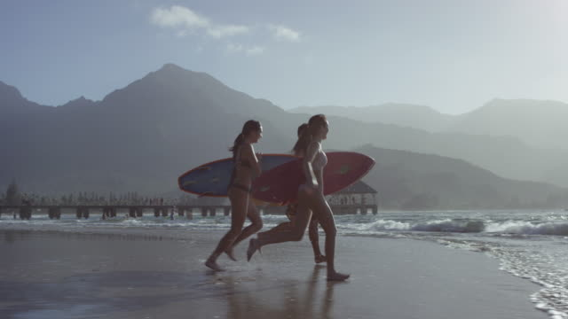 Friends surfing together on a tropical beach vacation to Hawaii