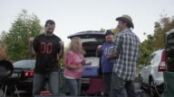 Friends tailgating, celebrating and dancing