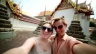 Friends taking selfie near Thai temples
