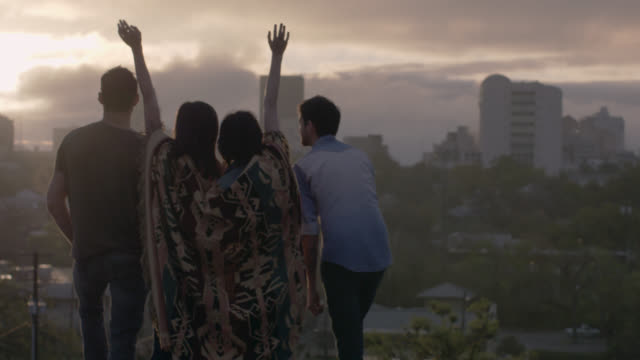Friends throw hands in the air and lean on each other overlooking downtown Austin, Texas