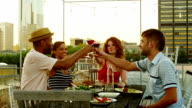 Friends toasting wine glasses dining at table on rooftop