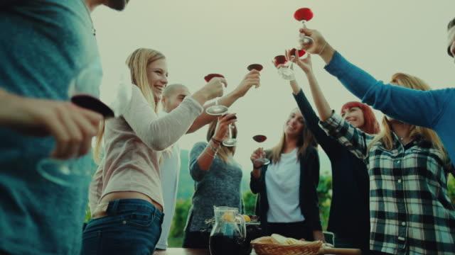 Vrienden samen genieten van maaltijd en rode wijn: de bril omhoog