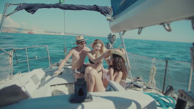 Friends together on a yacht sailboat cruising the sea