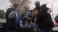 Friends trying to stay warm at a tailgating party