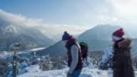 Friends walking through mountains in winter