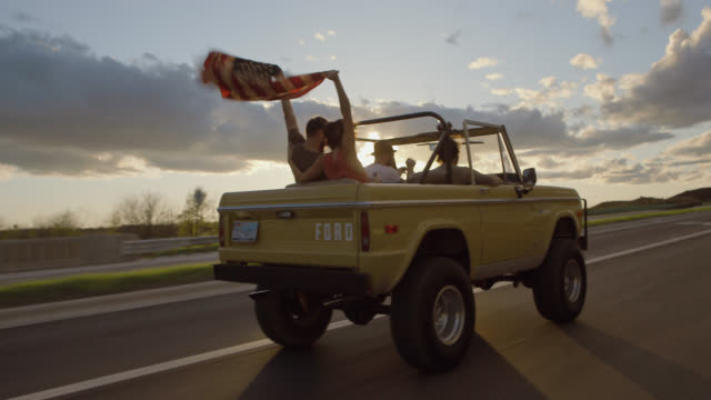 Friends wave American flag in the air in backseat of classic Ford Bronco
