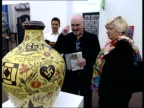 Frieze art fair in London's Regents Park Art collectors surveying pieces of art including Grayson Perry pot Neon lights on wall PAN to people...