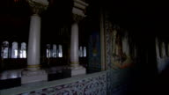 Friezes paintings pillars and chandeliers decorate an elaborate corridor inside a castle.\n Available in HD.