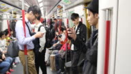 From a crowded street to the subway people checking their smart phones in the public transportation