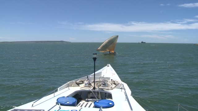 A POV from a sailboat's bow shows another small sailboat gliding across the ocean. Available in HD.