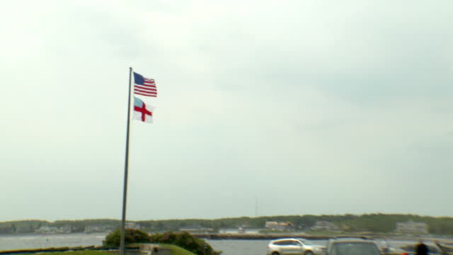 From American Episcopal Church flags on pole to large portable tent structure on waterfront grounds of St Ann's Episcopal Church as SUV slowly makes...