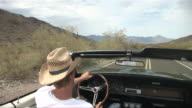 PASSENGER POV From back seat of convertible as man in straw hat drives down desert road/ Scottsdale, Arizona