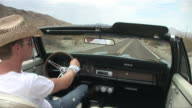 PASSENGER POV From back seat of convertible as man in straw hat drives down desert road and adjusts rear view mirror/ Scottsdale, Arizona