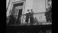 VS from below of Hayworth and Khan on balcony as photographers take photosÊ[exact month/day not known]