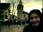 PAN from close up PORTRAIT senior woman in native dress to herd of goats in road / Sibiu, Transylvania