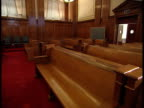 From empty gallery area to empty United States courtroom judge's bench plaintiff defendant tables jury box BG floor w/ red carpeting Law crime...