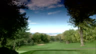 First hole fairway sloping green lined w/ trees Rocky Mountains distant BG
