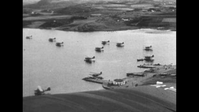 POV from German warplane carrying troops of another warplane carrying troops in flight / German soldiers in plane / aerial shot of fjord in Norway /...