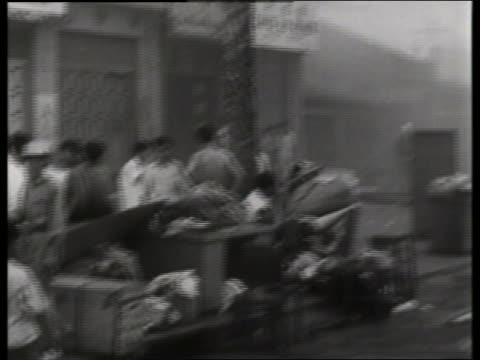 B/W PAN from group of Asians to smokefilled street / 1960's / Saigon / NO