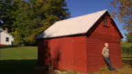 WS PAN From house to barn/ Man leaning against barn/ Livingston, New York