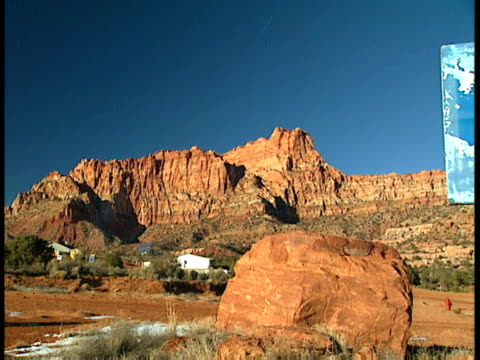 From large red field red rock mountain cliffs mountains BG to MS dilapidated outdoor basketball hoop backboard field BG Mohave County Arizona Strip AZ