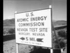 POV from lowflying camera plane of atomic bomb experiment area in NV with plane wing at top / sign indicating US Atomic Energy Commission test site /...