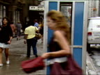 ZO from man in phone booth and pan to WS of intersection as people cross street on wet overcast summer day