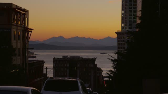 ZOOM OUT from MEDIUM to WIDE SHOT silhouetted mountains and Puget Sound with buildings in foreground at dusk