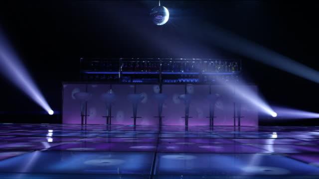 WS from nightclub dance floor toward bar lit up with flashing lights and disco ball