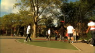 OFF SPEED Unidentifiable young teenagers playing basketball on outdoor court some young teens watching of frame Street ball bball