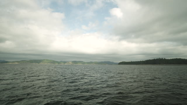 WS TD POV from Strait of Georgia of shoreline, with scattered clouds in sky and mountains in distance / Cortes, British Columbia, Canada