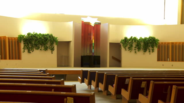 ZO from Torah ark to wide angle view of modern chapel interior with rows of benches in Jewish synagogue