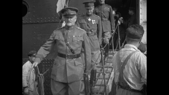 POV from vehicle carrying Gen John Pershing as he waves to crowds lining street / Pershing on deck of ship / Pershing disembarks down gangway...