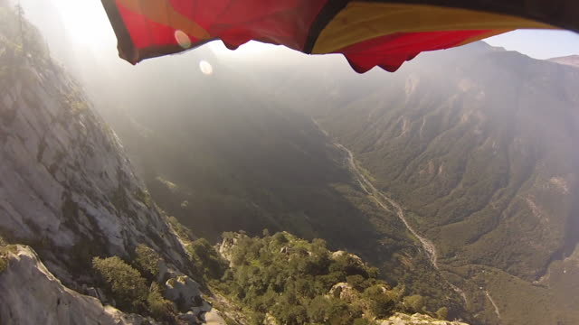 POV from wingsuit flyers foot as he flies over houses, cliffs and forest