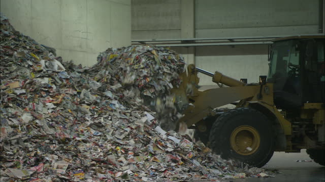 A front end loader scoops waste paper in a warehouse.