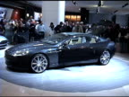 WS front end of Aston Martin Rapide concept car revolving on turntable / CU metallic license plate passing through frame / WS rear end of car...