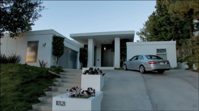 WS Front entrance to a white, square home with a car at the top of the driveway