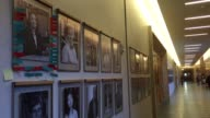 Front entrance to Harvard law school building with hallway of professor photos that were found vandalized with tape