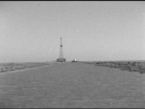 Moving up channel of coastal wetlands toward drilling rig derrick distant barge Note White spots some film lines Marshes Gulf Coast Louisiana bayous...