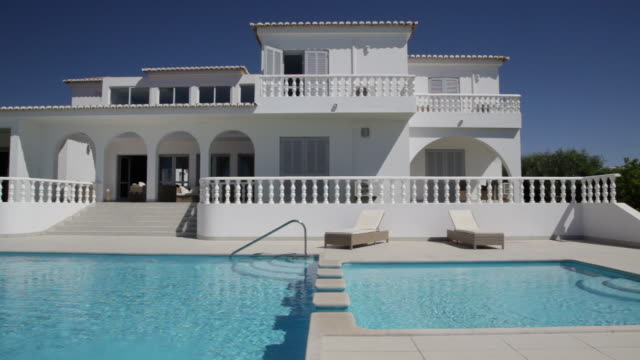 Front on across pool of white villa with colonnades and steps pool divider
